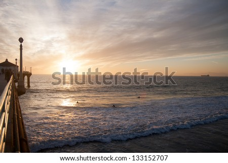 Surfers in the sunset near pier - stock photo
