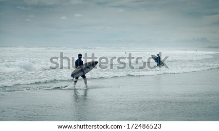 Surfers on Muriwai Beach - stock photo