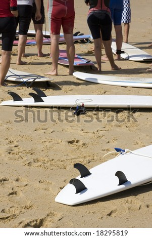 Surfers on the Beach with their Boards - stock photo