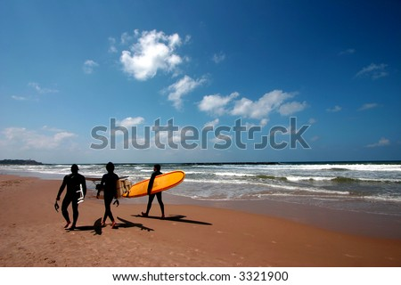 Surfers on tropical beach - stock photo