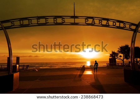 SURFERS PARADISE, AUS - AUS NOV 06 2014:Surfer silhouette walking to surf in Surfers Paradise beach.It's Australia's iconic coastal tourist destination located in Gold Coast Queensland, Australia. - stock photo