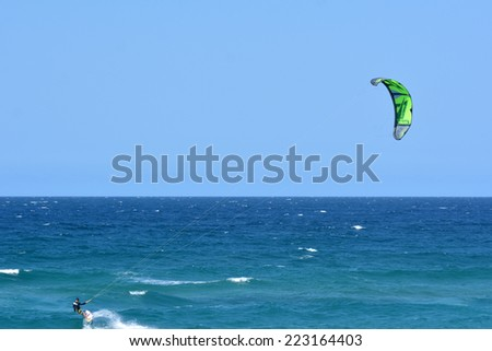 SURFERS PARADISE - SEP 30 2014:Kite surfers kitesurfing over the pacific ocean. Kitesurfing is a very popular water sport in Surfers Paradise in Queensland, Australia. - stock photo