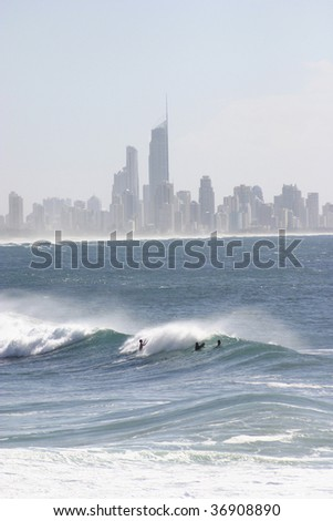 surfers playing on the gold coast,Q1 the worlds tallest residential building in the background - stock photo