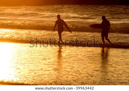surfers silhouette at the sunset - stock photo