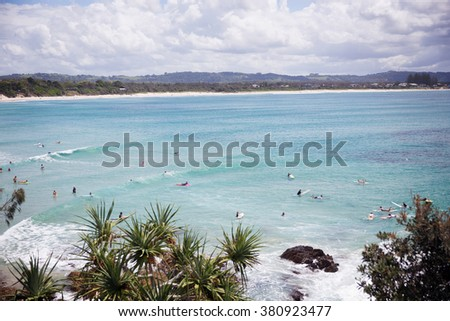 Surfers waited for a big wave in a turquoise bay under Australian sky - stock photo