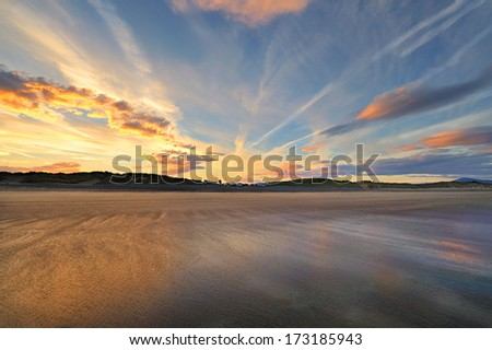 Surfers waiting for a wave, sunrise. Golden beach at the Brandon Bay, Dingle Peninsula, Ireland - stock photo