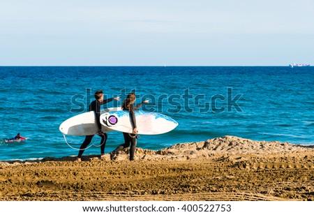 surfers walking along the beach - stock photo