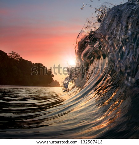 Surfing design template.  Green blue colored ocean surfing wave breaking and splashing at sunset time - stock photo