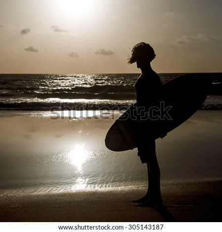 Surfing. Freedom. Travels. Surfer on the Beach at Sunset - stock photo