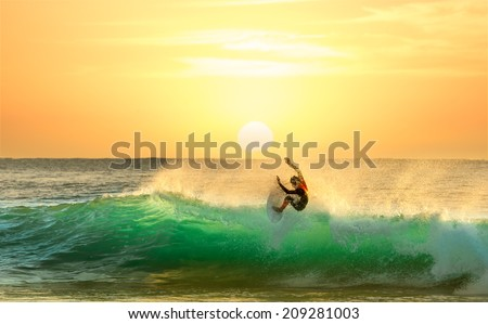 Surfing on a Green Wave with Sun Rising in the Background - stock photo
