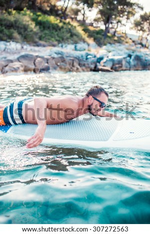 Surfing, surf, beach. Surfer Catching a wave  - stock photo