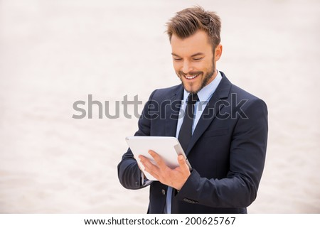 Surfing the net in desert. Cheerful young man in formalwear working on digital tablet while standing in desert - stock photo