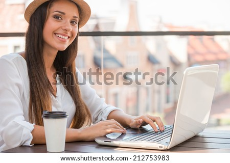 Surfing the net outdoors. Beautiful young woman in funky hat working on laptop and smiling while sitting outdoors - stock photo