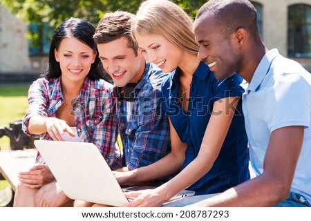 Surfing the net together. Four happy young people looking at laptop and smiling while sitting outdoors together - stock photo