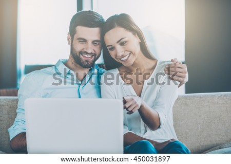 Surfing web together. Beautiful young loving couple sitting together on the couch and looking at laptop - stock photo