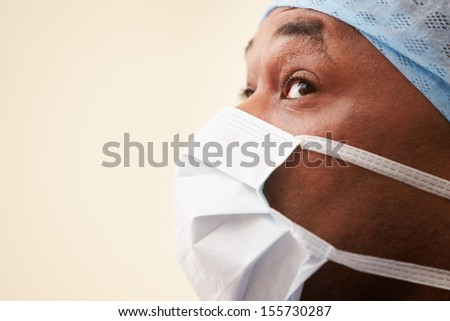 Surgeon In Operating Theatre Wearing Scrubs And Mask - stock photo