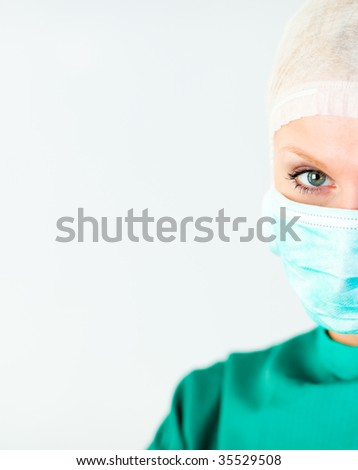 Surgeon with her mask and looking at the camera - stock photo