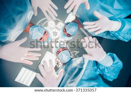 Surgeons standing above of the patient before surgery - stock photo