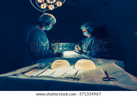 Surgeons team working with Monitoring of patient in surgical operating room. breast augmentation - stock photo