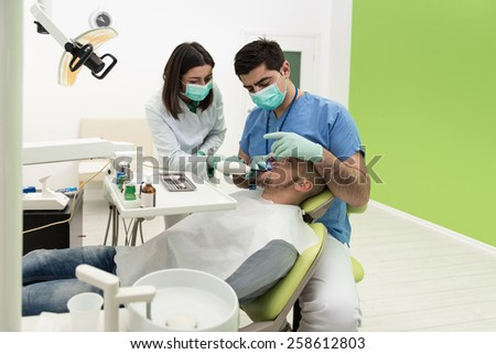 Surgery At The Dentist Office - Doctor Is Working On The Patients Mouth With The Help Of An Assistant - stock photo