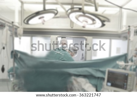 Surgery team operating in a surgical room-blurred - stock photo