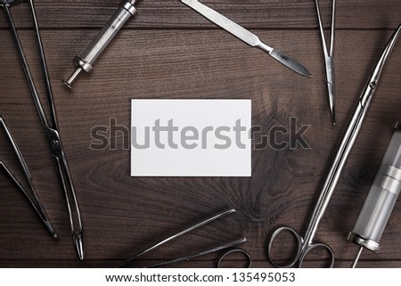 surgical armaments and blank notebook on the brown wooden table background - stock photo
