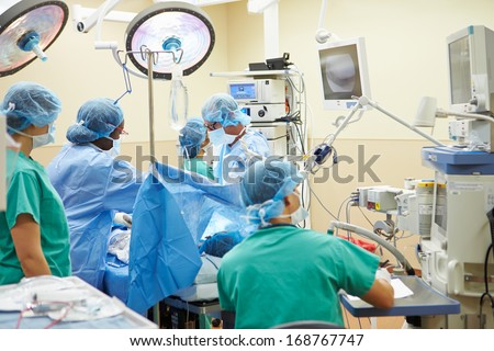 Surgical Team Working In Operating Theatre - stock photo