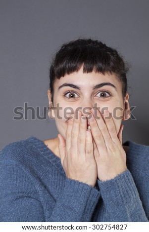 surprise and success concept - playful 20s woman wearing a blue winter sweater expressing herself with both hands on face,laughing for surprise and happiness - stock photo