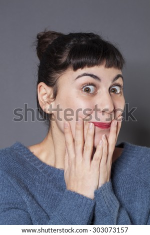 surprise and success concept - playful 20s woman wearing a blue winter sweater expressing herself with both hands on face,smiling for surprise and happiness - stock photo