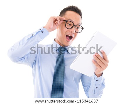 Surprise Asian business man looking at tablet computer, isolated over white background - stock photo
