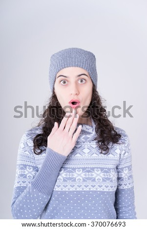 Surprise astonished woman in warm cloth. Closeup portrait woman looking surprised isolated grey wall background. Positive human emotion facial expression body language. Funny brunette girl - stock photo