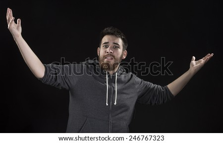 Surprise Goatee Young Man Wearing Gray Jacket with Arms Open While Looking at the Camera. Isolated on Black Background - stock photo