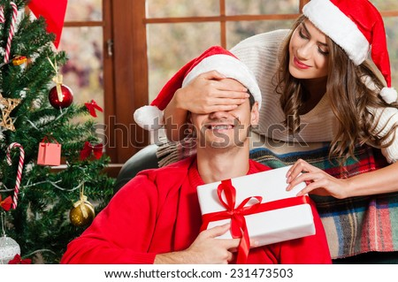 Surprise! Handsome young man sitting on the couch and holding a gift box while her girlfriend standing behind him and covering his eyes with hands and wering santa hat - stock photo