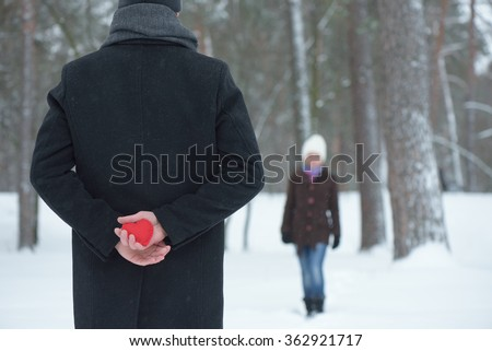 Surprise Valentines Day. Decorative heart in hands of Man. Meeting couple in winter park - stock photo