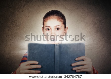 Surprised,Amazed cute little schoolgirl with a open book  isolated over grey background. - stock photo