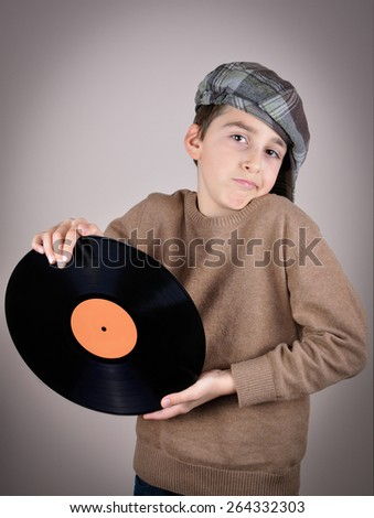 Surprised and amazed cute young boy wearing a brown sweater and tartan newsboy cap holding and showing a vinyl record. Isolated on gray background and added vignette. Vintage style photo - stock photo