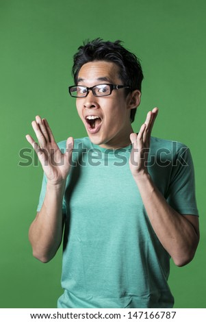 Surprised and amazed looking Asian man standing against green background. - stock photo