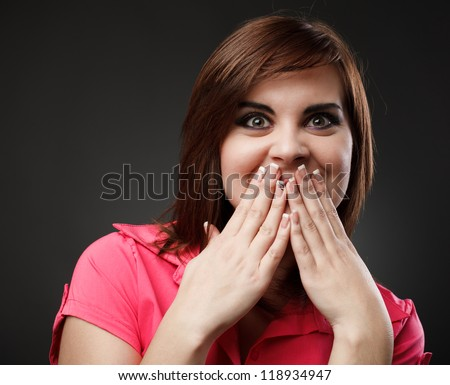 Surprised and amused young woman bursting in laugh - stock photo