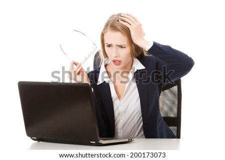Surprised and curious business woman cannot believe what she sees in the laptop screen. Isolated on white. - stock photo