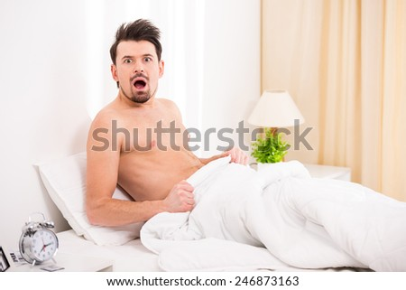 Surprised and shocked half naked young man in bed. - stock photo