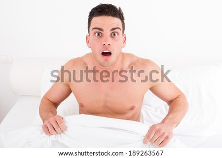 surprised and shocked half naked young man in bed  looking down at his penis under white covers sheet in bedroom. Concept photo of male sexuality and man sex problems, domestic atmosphere. - stock photo