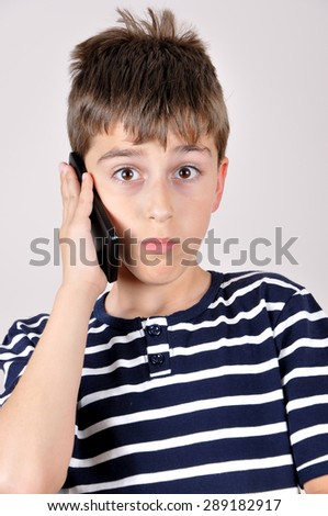 Surprised and wondering young boy talking on his smart phone - stock photo