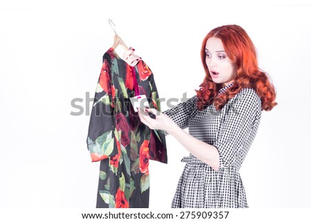 Surprised attractive woman disappointed with the price of the dress - stock photo