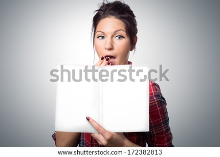 Surprised attractive young woman holding magazine with empty cover in her hand. - stock photo