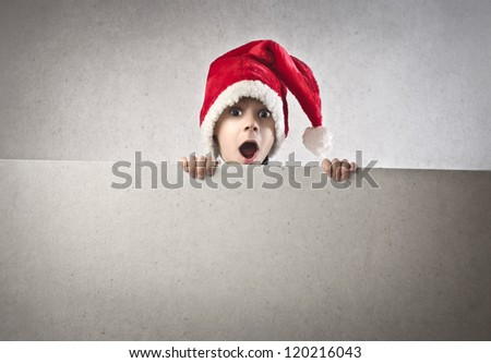 Surprised baby appearing over a white cardboard - stock photo