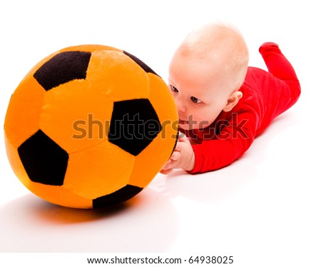 Surprised baby trying to get to the toy soccer ball - stock photo