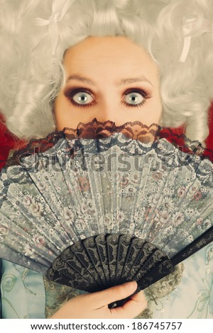 Surprised  Baroque Woman Portrait with Wig and Fan - Baroque style portrait of a surprised beautiful woman behind a hand fan  - stock photo