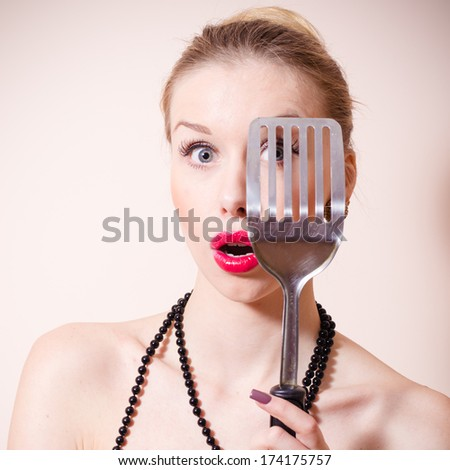 Surprised beautiful pinup woman looking through spatula amazed smiling & looking at camera - stock photo