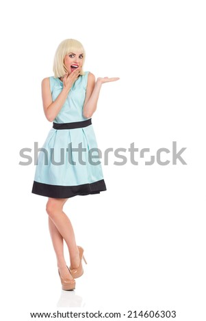 Surprised blond female in light blue color dress posing with hand raised. Full length studio shot isolated on white. - stock photo
