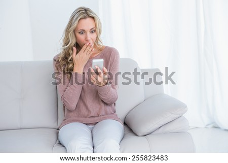 Surprised blonde sitting on couch reading message at home in the living room - stock photo